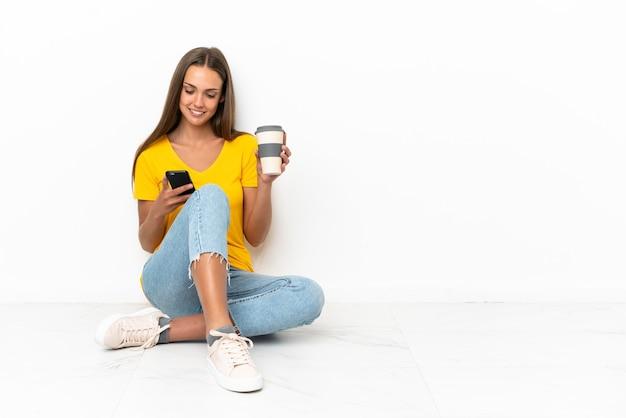 Młoda dziewczyna siedzi na podłodze trzymając kawę na wynos i telefon komórkowy
