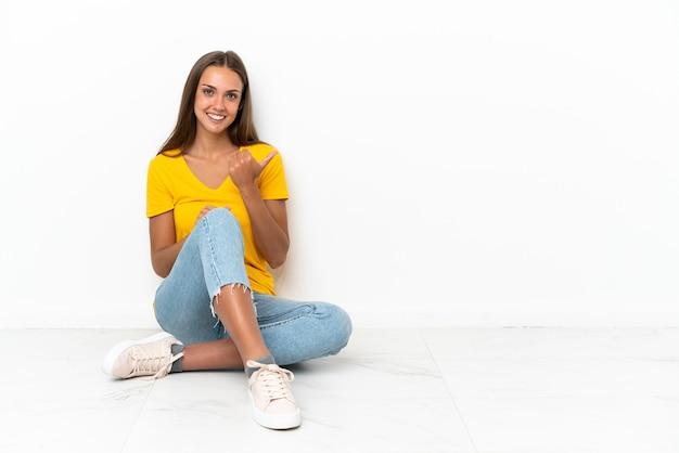 Młoda dziewczyna siedzi na podłodze, wskazując na bok, aby zaprezentować produkt