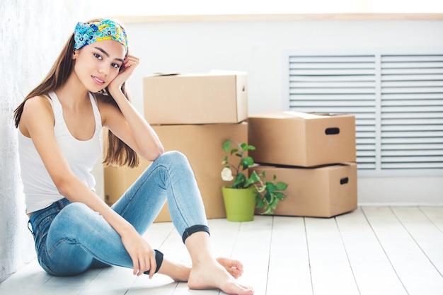 Młoda dziewczyna siedzi na podłodze z pudełkami do przenoszenia