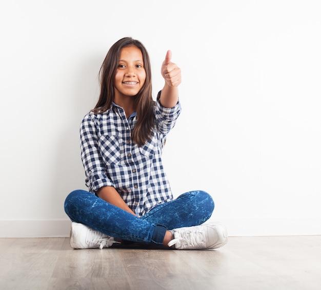 Młoda dziewczyna siedzi na podłodze z uśmiechem kciuki do góry