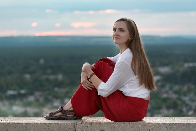 Młoda dziewczyna siedzi na tarasie widokowym. dziewczyna podróżuje sama.