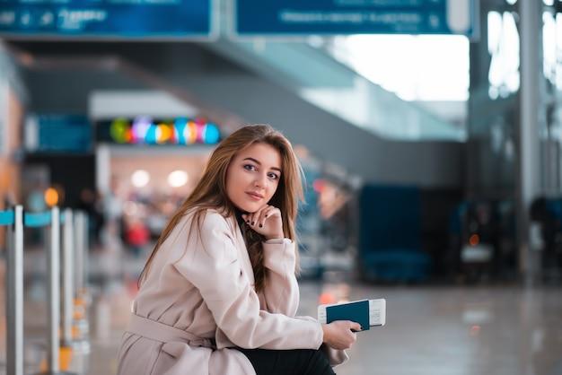 Młoda dziewczyna siedzi na walizce na lotnisku.