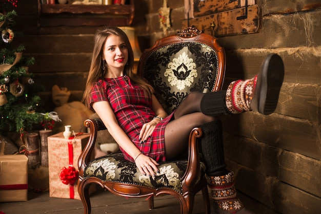 Młoda dziewczyna siedzi obok choinki i prezentów
