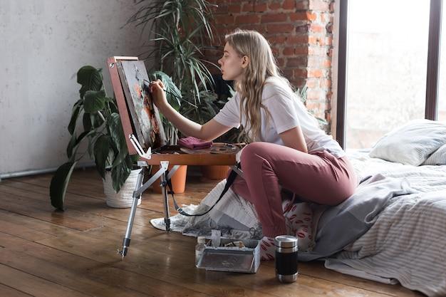 Młoda dziewczyna siedzi obok sztalugi rysunku obrazka z muśnięciem i paletą