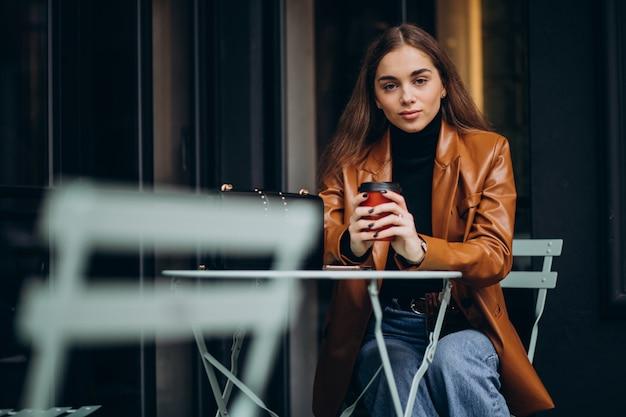 Młoda dziewczyna siedzi poza kawiarnią i picia kawy