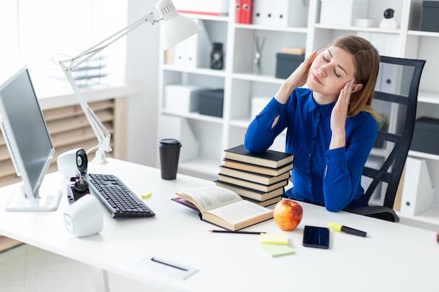Młoda dziewczyna siedzi przy biurku komputerowym i trzyma ręce za głową. przed dziewczyną leży otwarta książka.