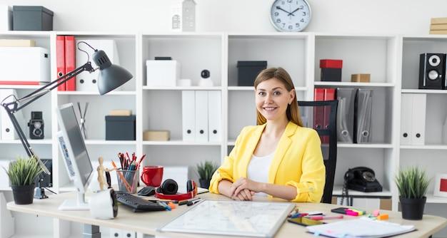 Młoda dziewczyna siedzi przy biurku komputerowym. przed dziewczyną stół jest tablicą magnetyczną.