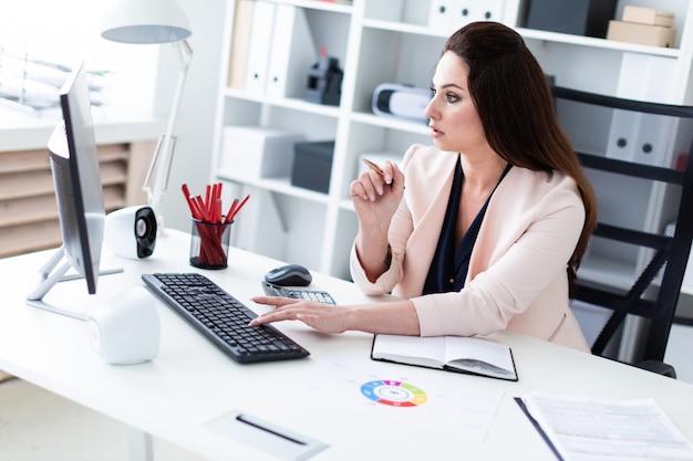 Młoda dziewczyna siedzi przy biurku komputerowym, trzyma długopis i pracuje z mapą i komputerem.