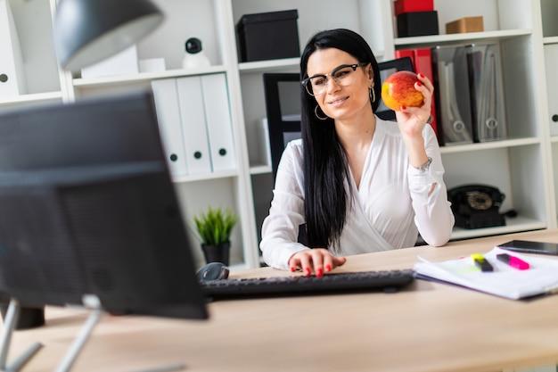 Młoda dziewczyna siedzi przy biurku komputerowym, trzyma jabłko w dłoni i drukuje na klawiaturze.