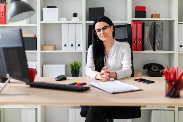 Młoda dziewczyna siedzi przy biurku komputerowym.