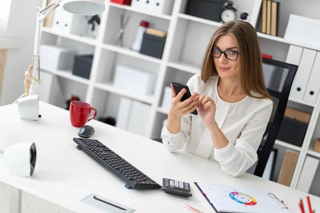Młoda dziewczyna siedzi przy biurku w biurze i trzyma telefon.