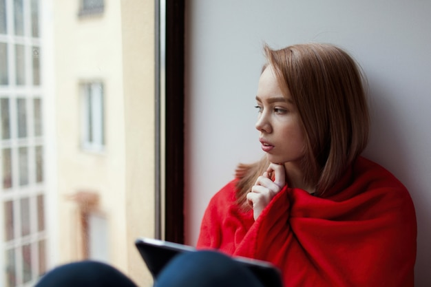 Młoda dziewczyna siedzi przy oknie.