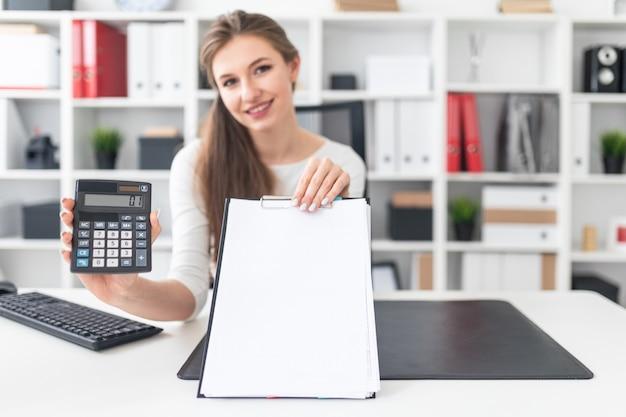 Młoda dziewczyna siedzi przy stole i trzyma kalkulator i pusty arkusz.