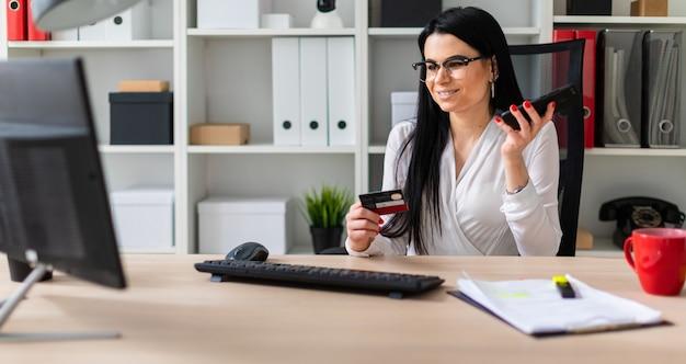 Młoda dziewczyna siedzi przy stole, trzymając kartę bankową i telefon.