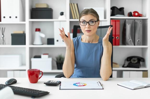 Młoda dziewczyna siedzi przy stole w biurze i patrzy na dokument z wykresem.