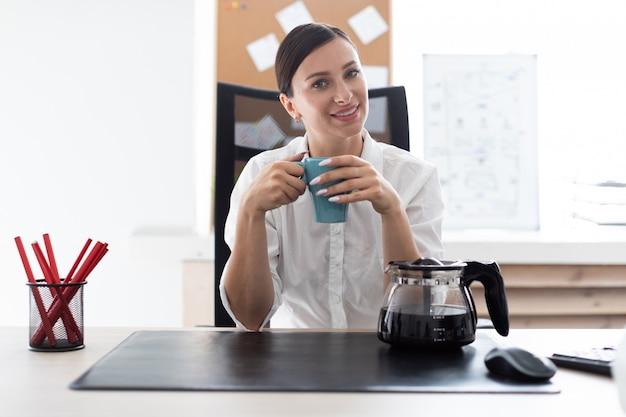Młoda dziewczyna siedzi przy stole w biurze i trzyma kubek.