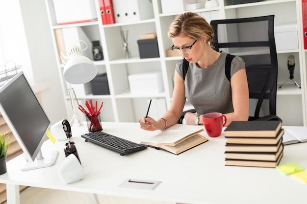 Młoda dziewczyna siedzi przy stole w biurze, trzymając ołówek w dłoni i czytając książkę.