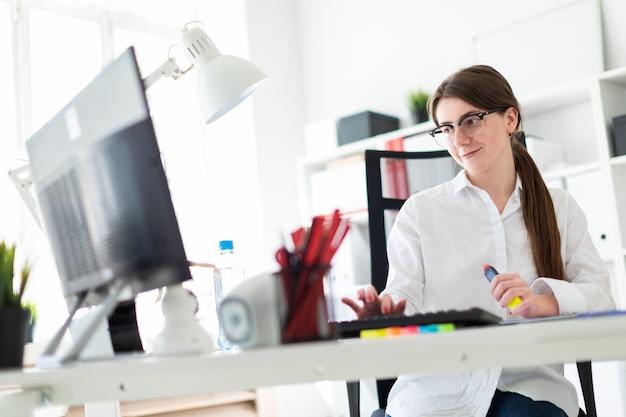 Młoda dziewczyna siedzi przy stole w biurze, trzymając w dłoni marker i wpisując tekst na klawiaturze.