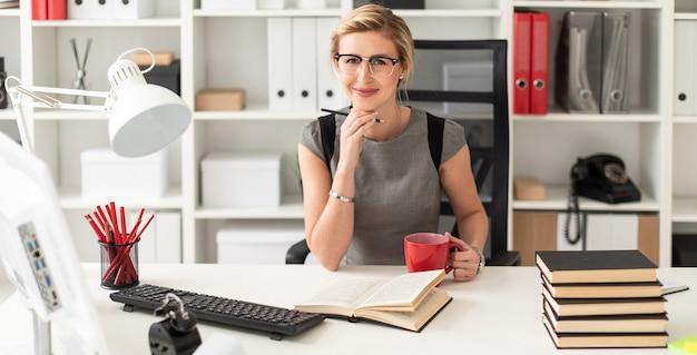 Młoda dziewczyna siedzi przy stole w biurze, trzymając w dłoni ołówek i czerwony kubek. przed dziewczyną leży otwarta książka.