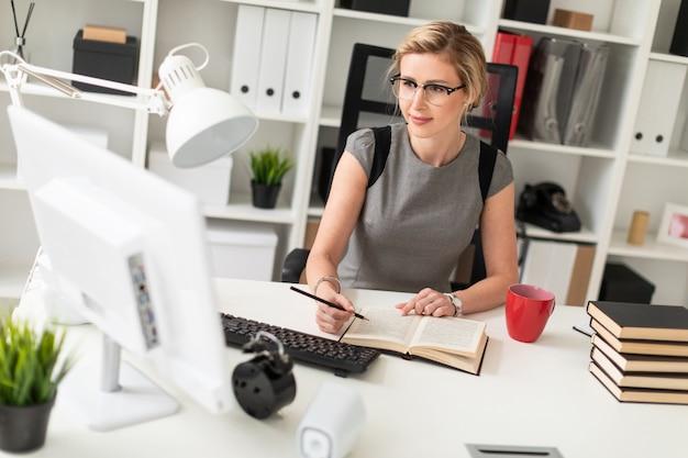 Młoda dziewczyna siedzi przy stole w biurze, trzymając w dłoni ołówek i czerwony kubek.