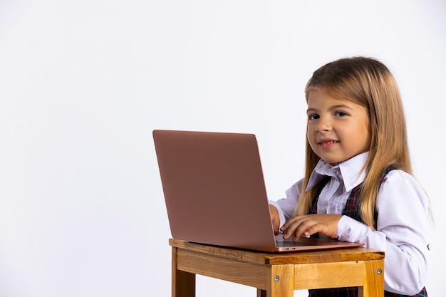 Młoda dziewczyna siedzi przy stole w domu, pracując nad jej pracą domową ze szkoły, wpisując odpowiedź na