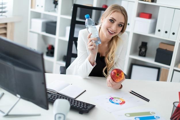 Młoda dziewczyna siedzi przy stole w swoim biurze i trzyma w rękach butelkę wody i jabłko.