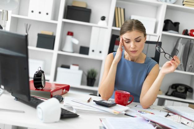 Młoda dziewczyna siedzi przy stole w swoim biurze i trzyma w ręku okulary.
