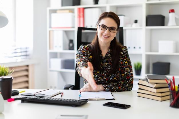 Młoda dziewczyna siedzi w biurze przy biurku komputerowym i sięga do przodu.
