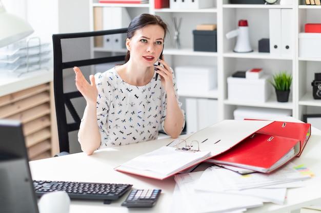 Młoda dziewczyna siedzi w biurze przy biurku komputerowym, pracuje z dokumentami i rozmawia przez telefon.