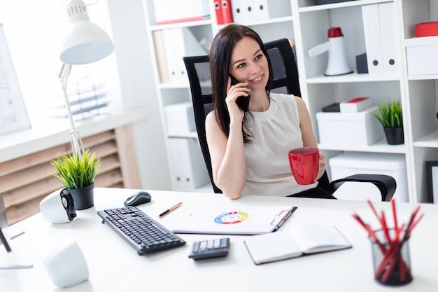 Młoda dziewczyna siedzi w biurze przy biurku komputerowym, rozmawia przez telefon i trzyma czerwony kubek.