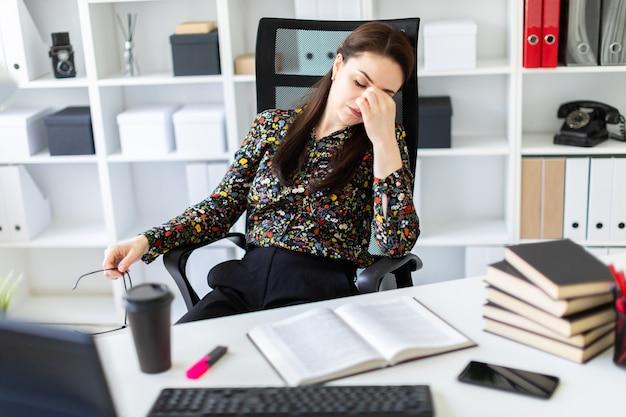 Młoda dziewczyna siedzi w biurze przy stole komputera.