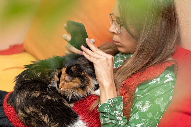 Młoda dziewczyna siedzi w domu na kanapie z kotem leżącym na niej i ze smartfonem w dłoniach i patrząc w to. strzał został wykonany przez zielone liście roślin domowych. selektywny nacisk na kota.