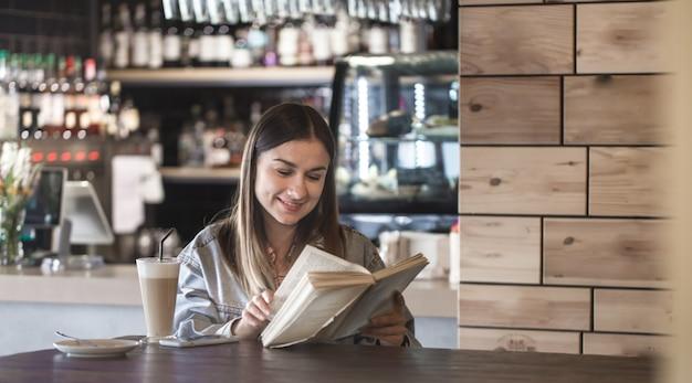 Młoda dziewczyna siedzi w kawiarni, czytając książkę i pije latte
