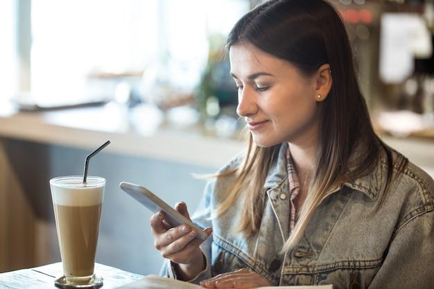 Młoda dziewczyna siedzi w kawiarni, picia kawy i patrząc na telefon