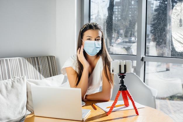 Młoda dziewczyna siedzi w kawiarni w masce i prowadzi wideoblog. komunikacja z aparatem.