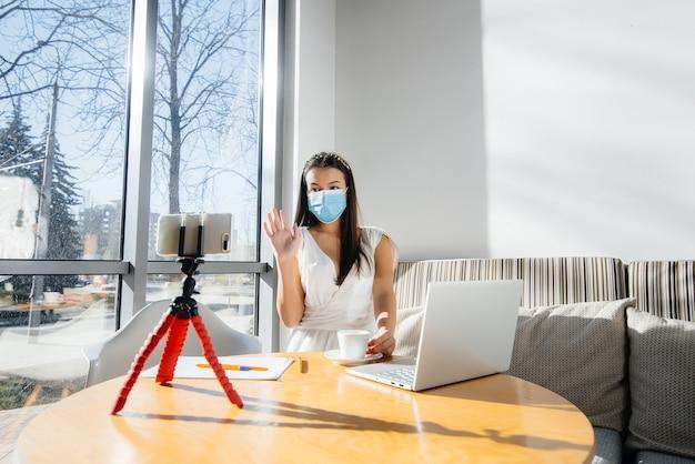 Młoda dziewczyna siedzi w kawiarni w masce i prowadzi wideoblog. komunikacja z kamerą.