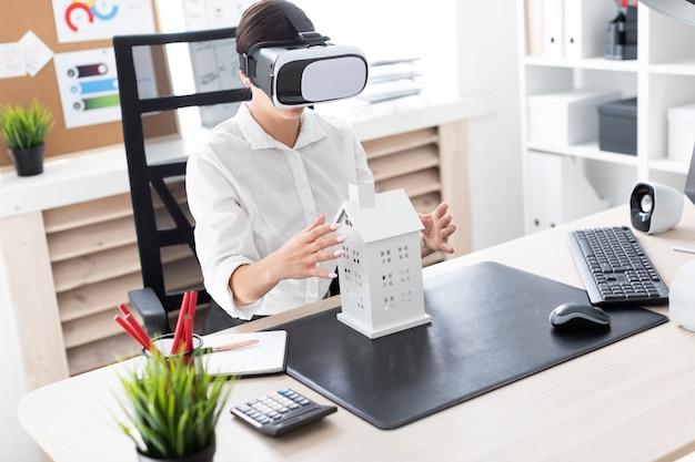 Młoda dziewczyna siedzi w okularach wirtualnej rzeczywistości. przed nią na stole jest układ domu.