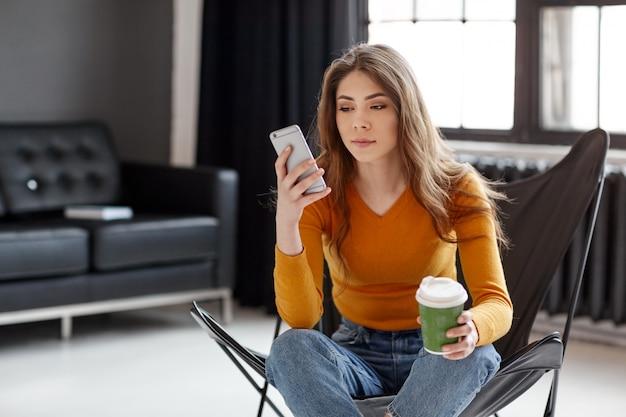 Młoda dziewczyna siedzi w stylowym czarnym skórzanym fotelu, trzyma w dłoni filiżankę kawy i telefon. praca, komunikacja, relaks w domu