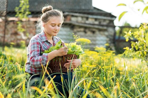 Młoda dziewczyna siedzi w widoku z boku trawy