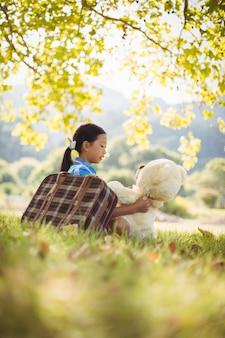Młoda dziewczyna siedzi z misiem i walizką