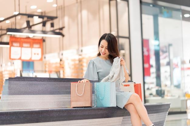 Młoda dziewczyna siedziała i patrzyła na rzeczy, które kupiła w centrum handlowym