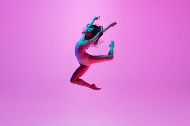 Młoda dziewczyna skacze na różowej ścianie