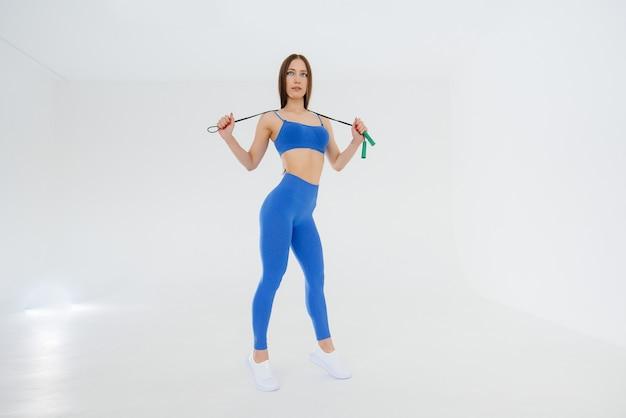 Młoda dziewczyna skacze przez skakankę w niebieskim dresie na białym tle. fitness, zdrowy styl życia.