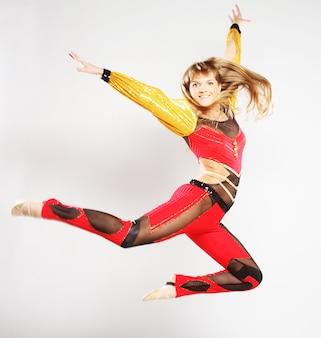 Młoda dziewczyna skacze w tańcu gimnastycznym