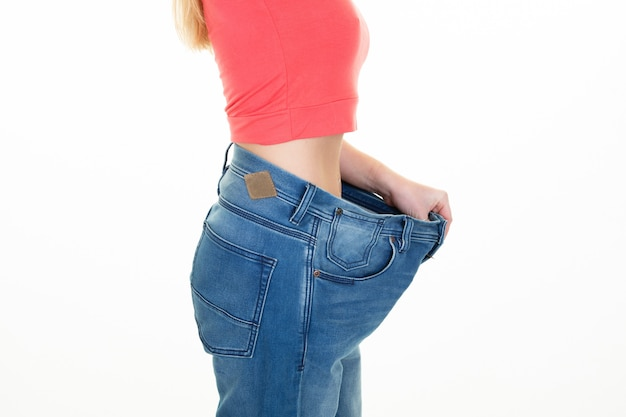 Młoda dziewczyna slim fit w profilu jeansy oversize w białym tle