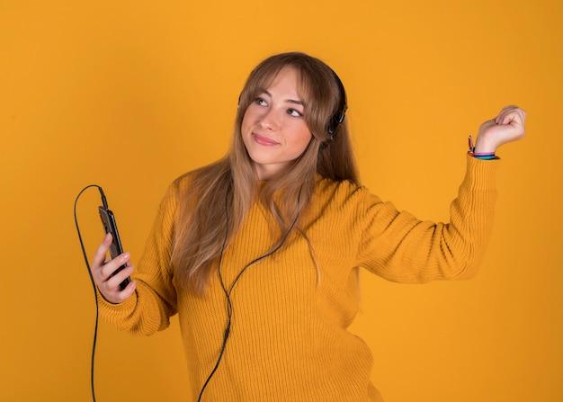 Młoda dziewczyna słucha muzyka na jej smartphone szczęśliwym z hełmofonami na żółtym tle