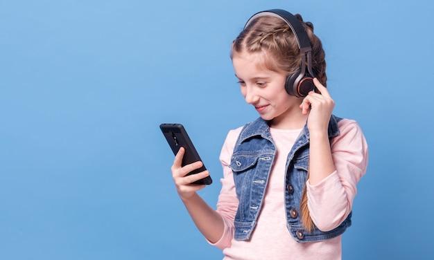 Młoda dziewczyna słucha muzyka z hełmofonami