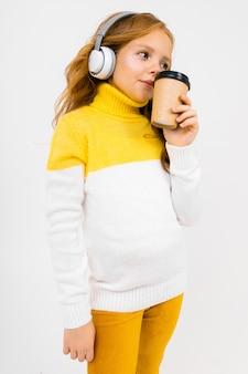 Młoda dziewczyna słucha muzyki w dużych słuchawkach i pije kawę