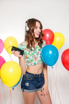 Młoda dziewczyna słucha muzyki ze słuchawkami obok balonów