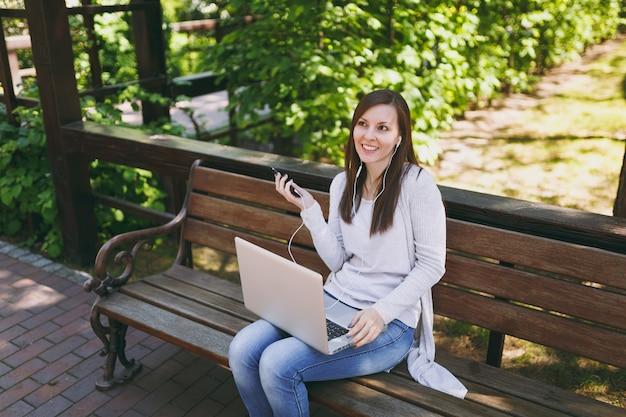 Młoda dziewczyna słuchać muzyki w telefonie komórkowym ze słuchawkami. kobieta siedzi na ławce, pracując na nowoczesnym komputerze przenośnym w parku miejskim na ulicy na zewnątrz na przyrodzie. biuro mobilne. koncepcja biznesowa freelancer